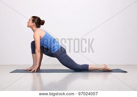 Beautiful sporty fit yogini woman practices yoga asana  Anjaneyasana - low crescent lunge pose in surya namaskar in studio