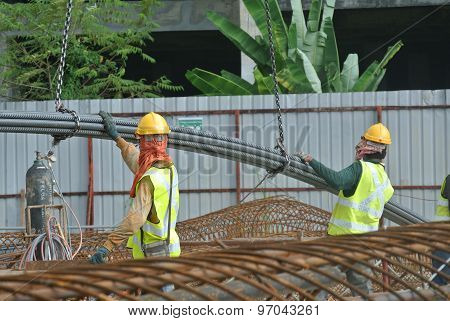Construction workers using crane to lifting heavy reinforcement bar