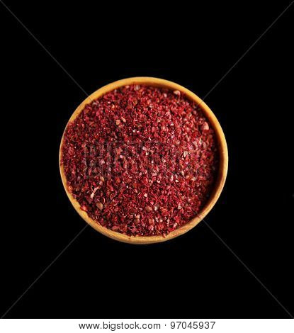 Sumac in wooden bowl, isolated on black