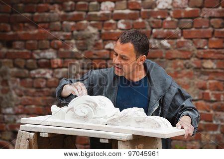 craftsman restorer working with gypsum model