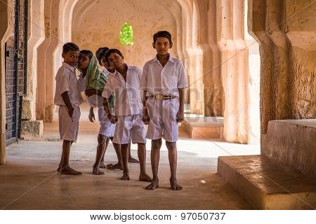 HAMPI, INDIA - 30 JANUARY 2015: Five schoolboys stand inside Queens's bath ruins.