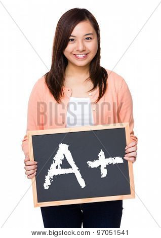 Asian woman with black board showing a A plus mark