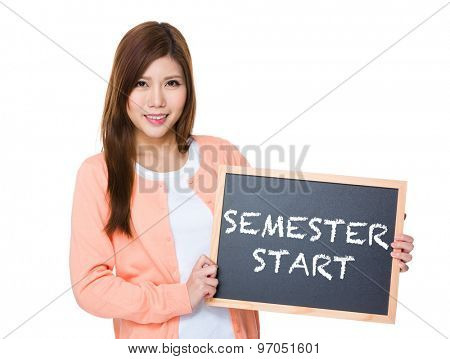 Woman hold with blackboard showing phrase of semester start