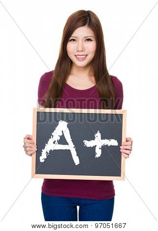 Woman hold with blackboard showing a A plus mark