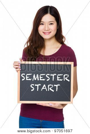 Asian Young woman hold with chalkboard and showing phrase of semester start