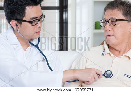 Doctor and patient. Sick Asian elder man consult family doctor, sitting on sofa. Senior retiree indoors living lifestyle.