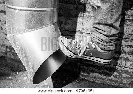 Teenager In Sneakers Kicks Drainpipe, Black And White