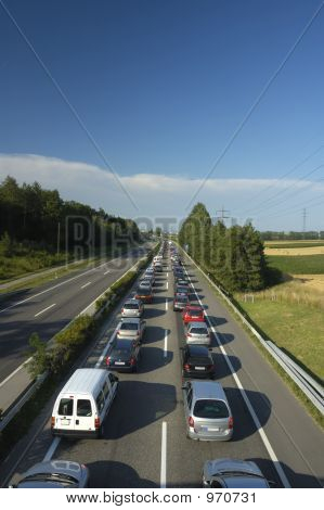 a line of stationary traffic stretches away into the distance on one side of the freeway (motorway autoroute autobahn) whilst in the other direction it is completely clear. poster