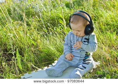A little boy sitting in a meadow in the headphones. The day is bright and sunny. The kid looks at the grass. poster