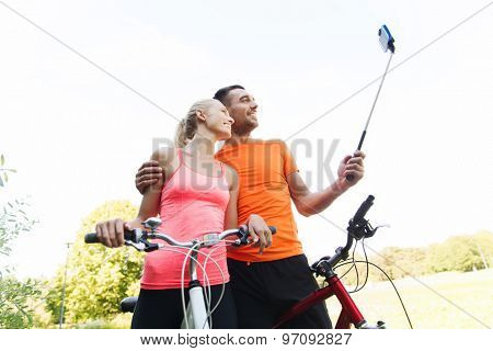 fitness, sport, people, technology and healthy lifestyle concept - happy couple with bicycle taking picture by smartphone on selfie stick outdoors