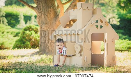 boy playing in cardboard house