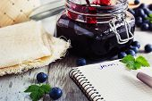 homemade blueberry jam in a jar and fresh blueberries on a table. a place for inscriptions. toning vintage style.health and diet concept. selective focus poster