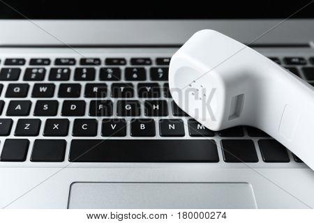 Modern laptop and telephone handset closeup
