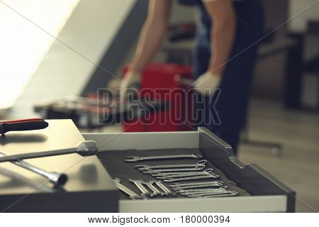 Drawer unit with tools in car repair shop and blurred auto mechanic on background