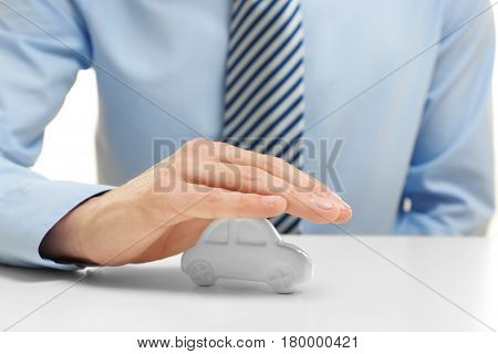 Insurance concept. Man covering toy car on table
