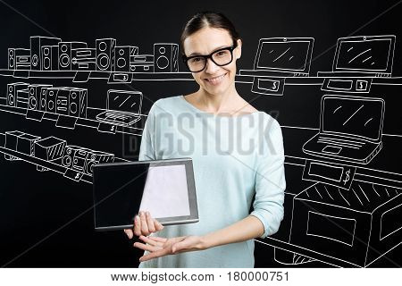 The best model. Cheerful professional shop assistant holding tablet and working in a shop while selling electronics