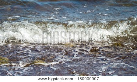 Cold blue sea water surf over seashore. Chilly sea wave splashes over coast. Strong oceanic current. Minimal seascape for travel background. Dangerous sea. Summer travel outdoor threat concept image