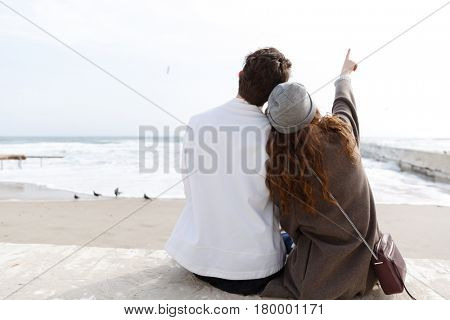 Back view of beautiful young couple sitting on the beach in autumn and pointing away