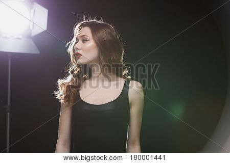 Charming young woman with red lips standing near studio spotlight and looking away over black background