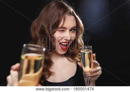 Cheerful charming young woman giving you glass of champagne and winking over black background