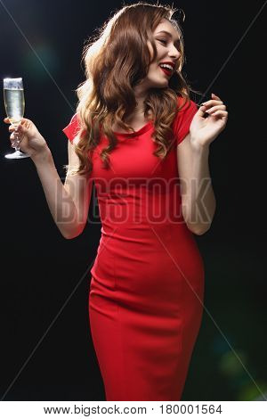 Cheerful attractive young woman in red dress dancing and drinking champagne over black background