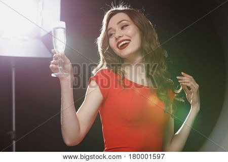 Cheerful attractive young woman in red dress holding glass of champagne over black background