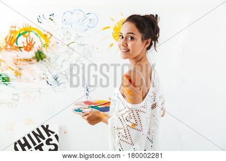 Happy young woman with palette and brushes painting over white background