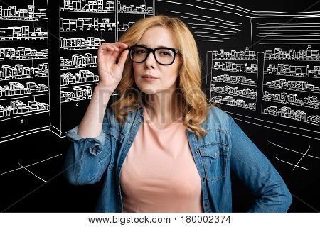 Be attentive with it. Professioanl concentrated female pharmacist holdign her glasses and working in the drug store