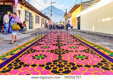 Antigua, Guatemala - April 2 2017: Dyed sawdust procession carpets during Lent against backdrop of Agua volcano in colonial town with most famous Holy Week celebrations in Latin America.