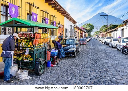 Antigua, Guatemala - April 2 2017: Fruit seller colorful houses & Agua volcano in colonial city & UNESCO World Heritage Site of Antigua during Lent.