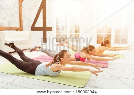 Creating flexible bodies. Young-looking pretty ladies lying on floor and leaning up with their arms while doing stretching.