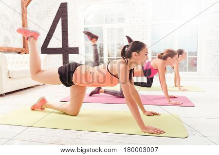 Creating dream body. Side view of youthful women group doing stretching by lying on floor and lifting one leg up at sports club.