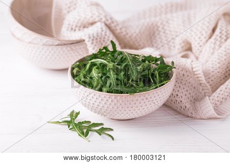 Fresh Green Arugula In Bowl On Wooden Table.