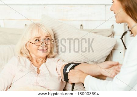 Full of care. Proficient capable young caregiver sitting in the bedroom and helping old woman while measuring her blood pressure