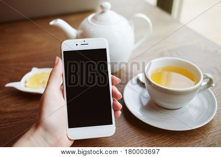 White cup of tea with lemon, woman's hand is holding phone mobile smart phone. Brawn wooden table background. Top view with copy space on phone screen. Healthy drink concept