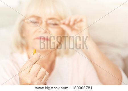 Taking care about myself. Attentive charming old lady sitting at home and holding the pill while touching glasses and expressing interest
