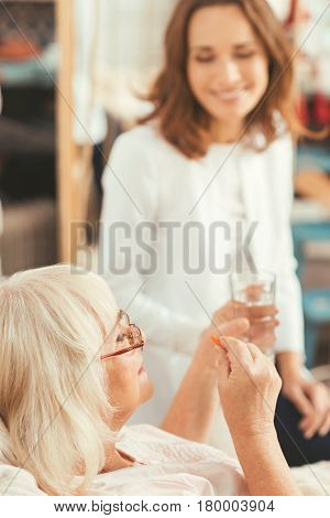 Time for important medicaments. Involved old attentive pensioner lying in the bedroom and taking pill while young nurse sitting next to the bed