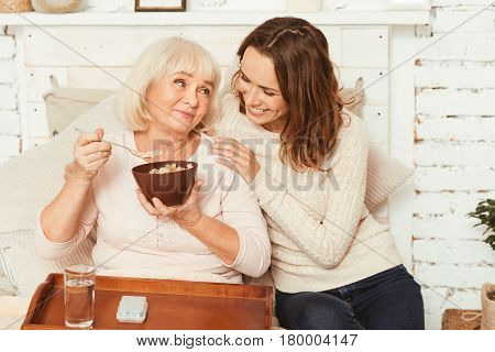 Leading positive lifestyle together. Cheerful delighted young woman sitting in the bedroom and hugging old grandmother while offering breakfast