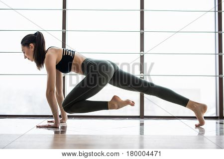 Full Length Of Young Beautiful Woman In Sportswear Doing Plank While Standing In Front Of Window At