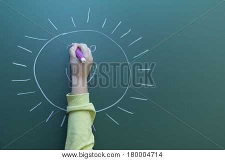 Kid drawing happy face to the greenboard with chalk