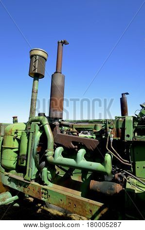 The manifold of an old green tractor is exposed with the removal of the hood plate cover