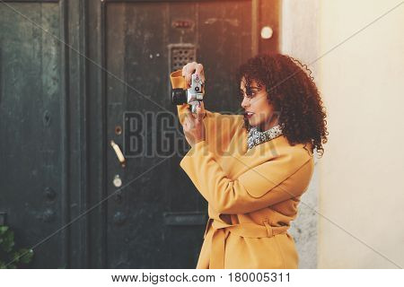 Concentrated beautiful amateur curly professional journalist photographer in yellow trendy coat photo shooting for newspaper using vintage film camera on sunny street of European city near doors