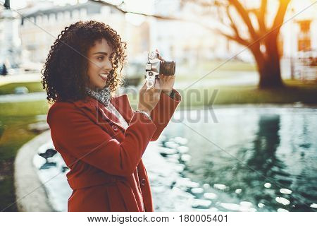 Concentrated beautiful adult curly professional photographer in red trendy coat making photos using retro film camera near city pond on sunny day with copy space for your advertising text message