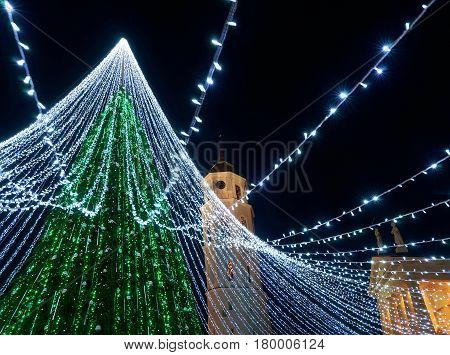 Christmas tree with decoration and Bell tower at Cathedral Square Vilnius Lithuania. It has fairy lights as if bridal veiling. Illuminated at night