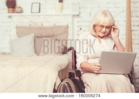 Testing modern gadget. Skilled aging enable woman sitting in the wheelchair at home while expressing interest and using laptop