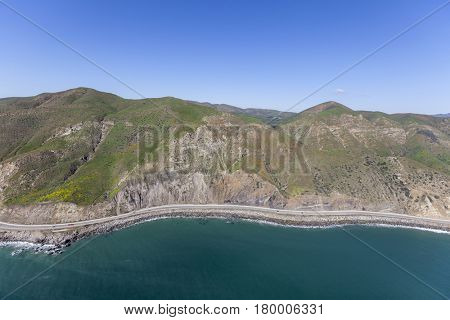 Aerial view of Pacific Coast Highway and rugged cliffs north of Malibu near Los Angeles, California.
