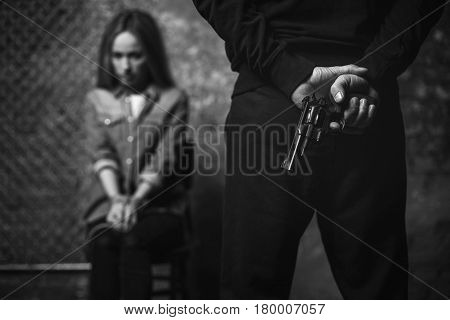 You cannot run. Savage barbaric violent criminal guarding a woman whom he holding hostage while hiding a gun behind his back