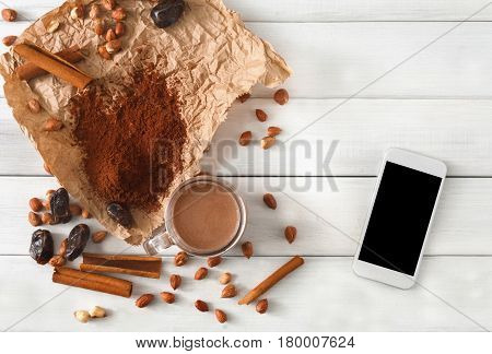 Order online detox cleanse drink, chocolate smoothie ingredients. Natural, healthy nutrition. Cocoa powder, nuts, date fruit mix on white wood with mobile screen for copy space, top view