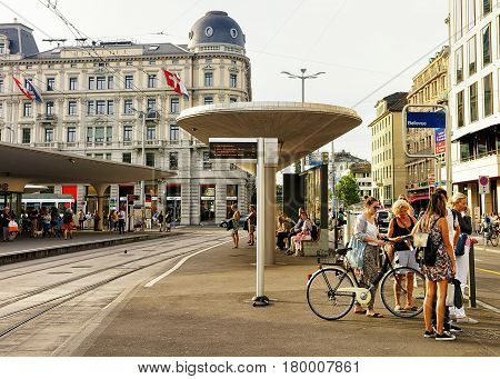 People At Bellevue Bus Stop In Zurich City Center