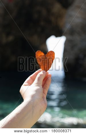 Woman hand holding heart shaped leave in Antiochia ad Cragum in Turkey with rocks and sea blurred as background